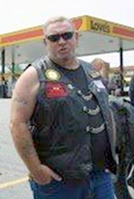 Large tall white male short blond hair wear glasses, leather biker jacket with patches: deceased.