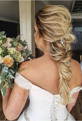 Uylana Aster Bridal Hair Styles Brides in wedding gown standing holding flowers with romantic bridal hair and hair vine in her hair bridal earrings