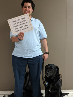 Man with dog holds campaign sign