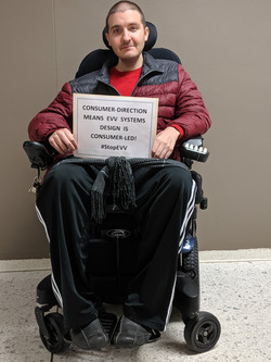 Wheelchair user holds campaign sign