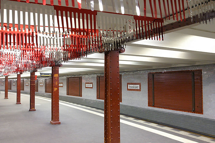 """Red and silver pennant chains were attached to the ceiling of the subway station, and they began to flutter when the trains arrived. This caught the attention of the passengers like an advertisement would but was not linked to any product. The work, which is titled Typenoffen (""""Type Open""""), offered nothing concrete for the passenger's attention to grasp, instead encouraging them to reflect critically on the ubiquitous presence of advertising in the public space."""