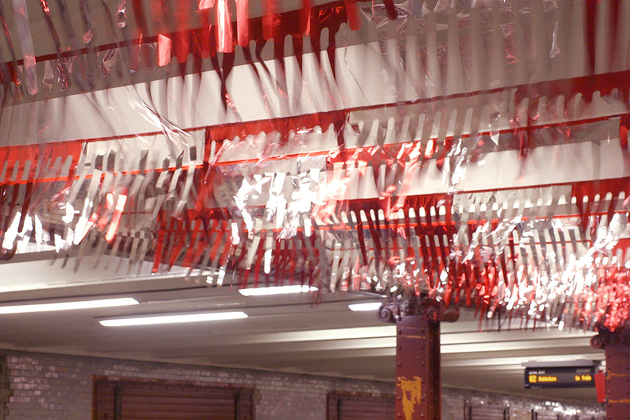 "Red and silver pennant chains were attached to the ceiling of the subway station, and they began to flutter when the trains arrived. This caught the attention of the passengers like an advertisement would but was not linked to any product. The work, which is titled Typenoffen (""Type Open""), offered nothing concrete for the passenger's attention to grasp, instead encouraging them to reflect critically on the ubiquitous presence of advertising in the public space."