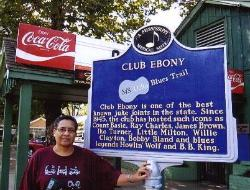 Mary Shepard in front of older sign at C