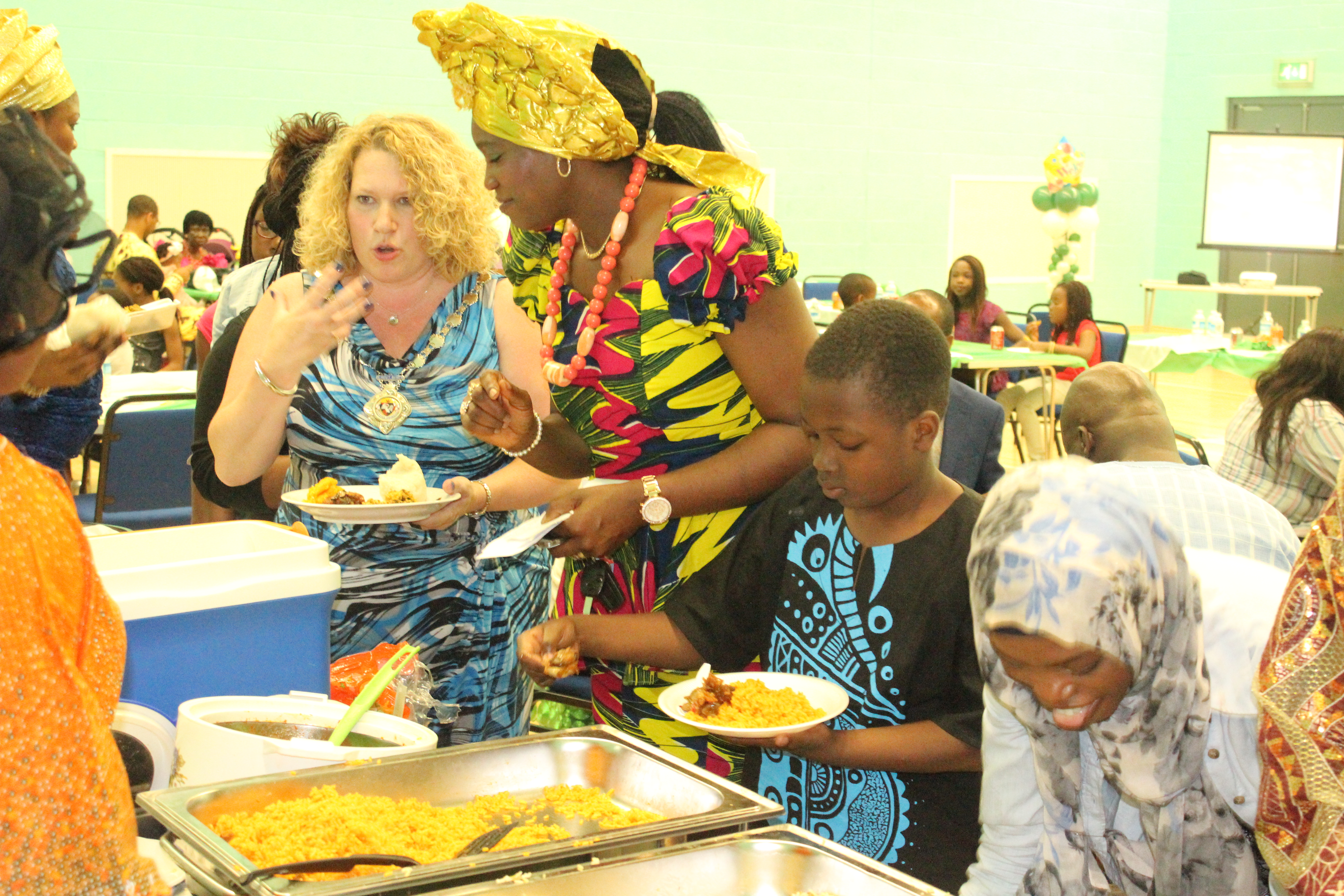 Queen helping Cllr Allison with Nigerian food