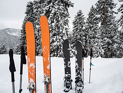 Mountain skis, splitboard and poles in s
