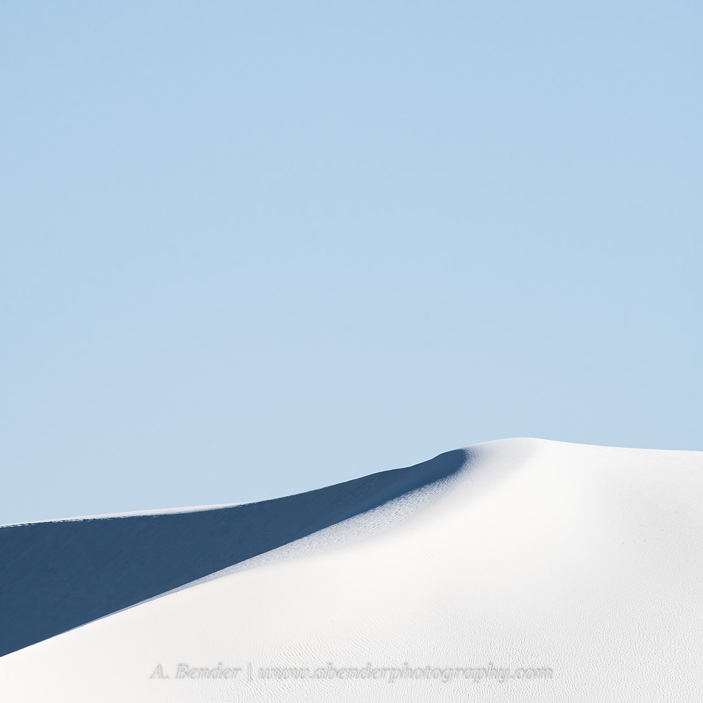 Minimalist image of a white gypsum sand dune peak against light blue sky in White Sands National Park Monument in New Mexico   A Bender Photography LLC