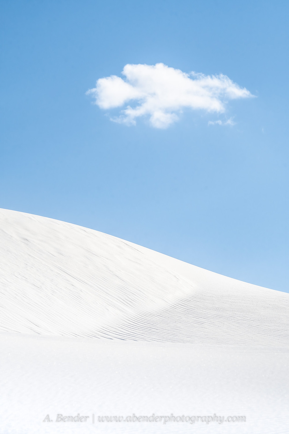 A single cloud floats over the white gypsum sand dunes against blue sky in White Sands National Park, NM   A Bender Photography LLC