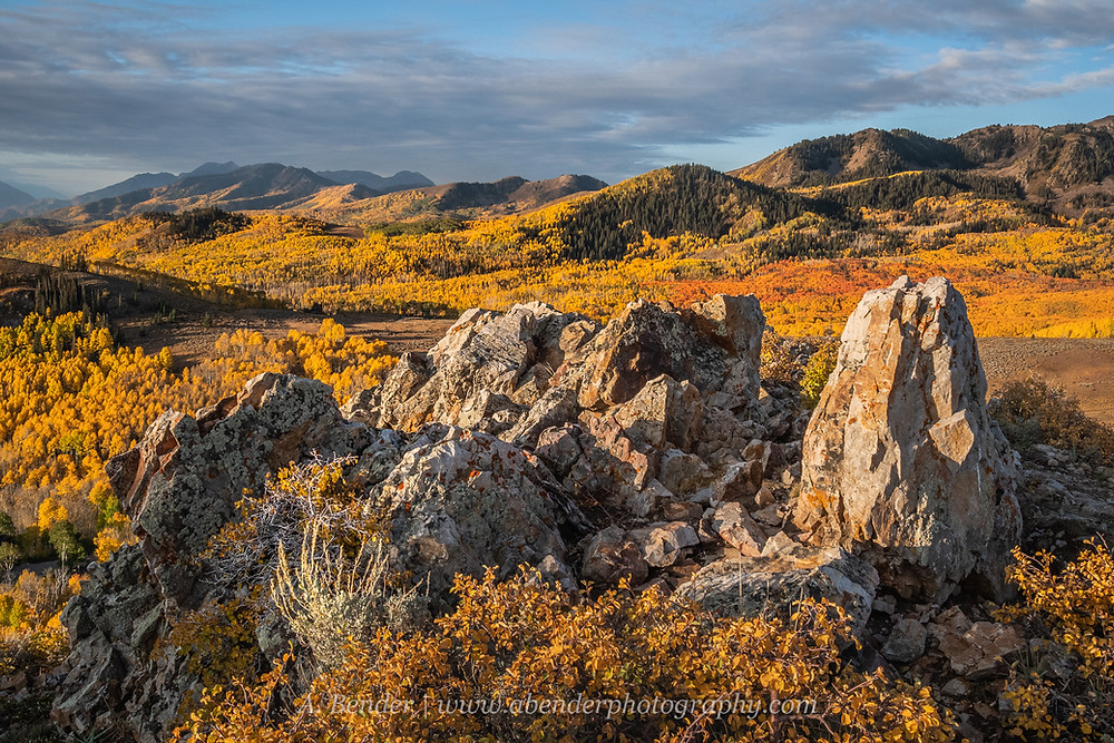 Wasatch Mountains Utah view with 2021 fall foliage at sunrise with clouds in the sky, prominent rock formation in the foreground | A Bender Photography LLC