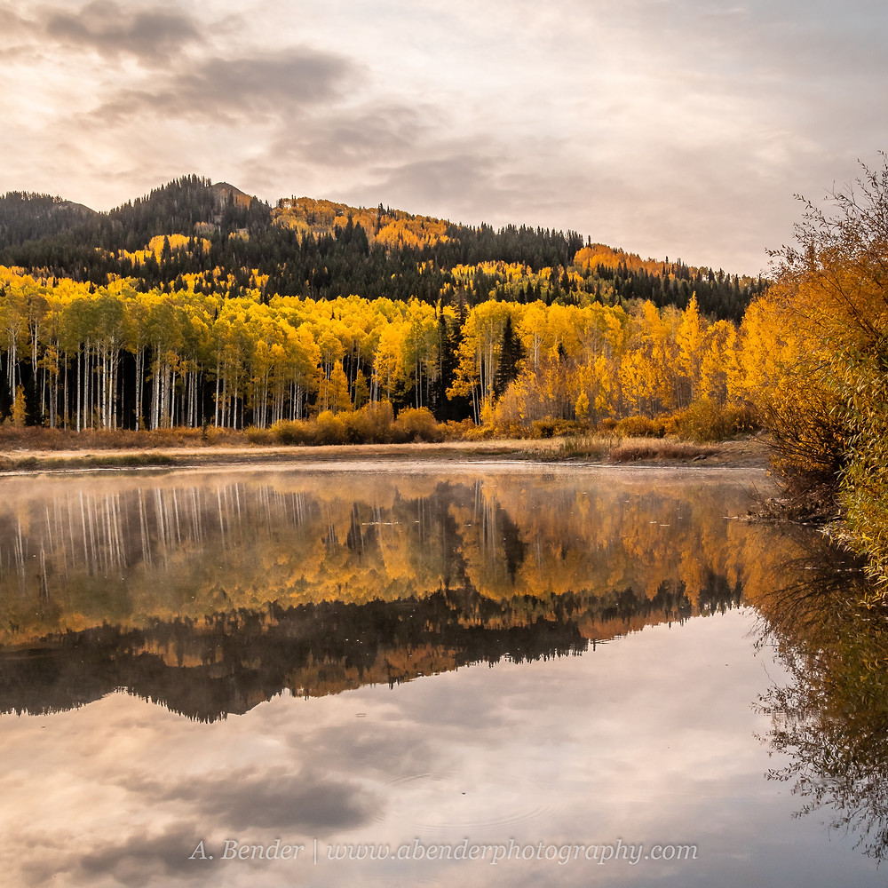Stormy skies over a scene of fall colored aspen reflecting in a lake in the Wasatch Mountains Utah | A Bender Photography LLC