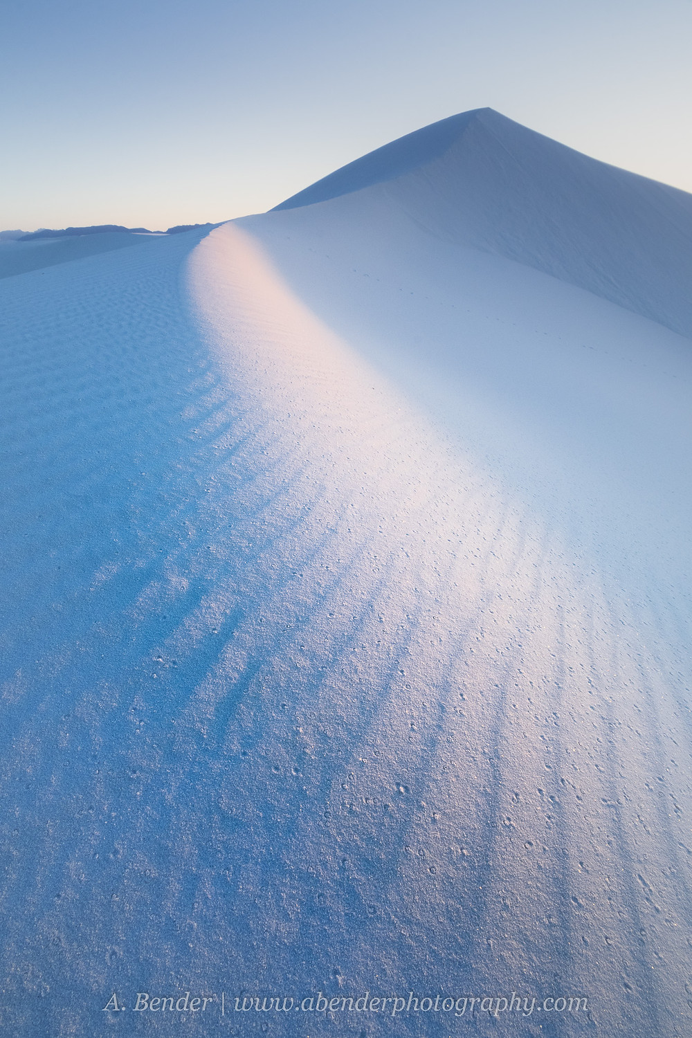 Gypsum sand dune reflecting blue skies at White Sands National Park at sunset   A Bender Photography LLC