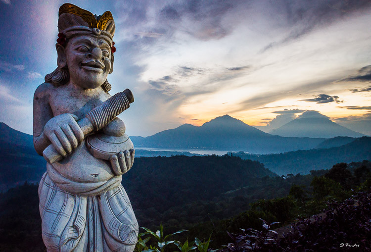Sunrise over the volcanoes with Balinese statue in the foreground.