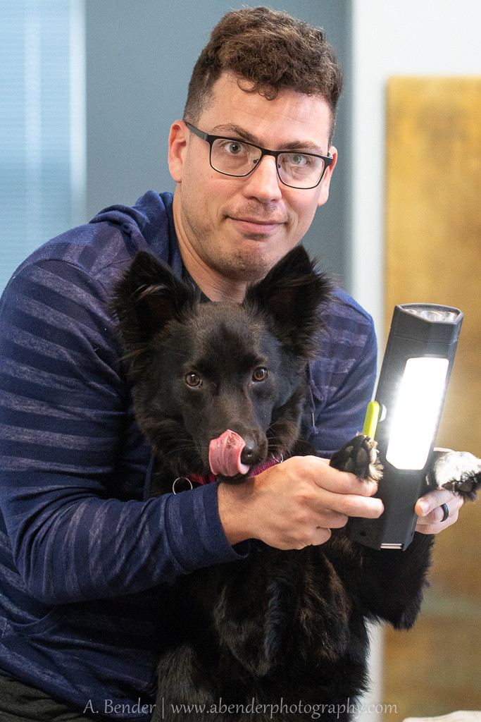 husband and dog helping hold a light