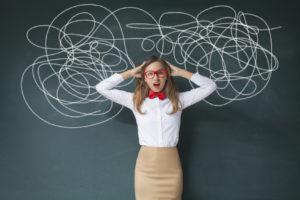 Portrait of confused businesswoman on blackboard