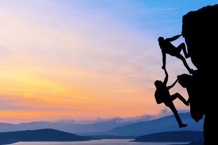 The joint work teamwork of two travelers help each other on top of a mountain climbing team, a beautiful sunset landscape