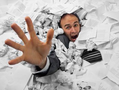 Businessman sinking in heap of documents
