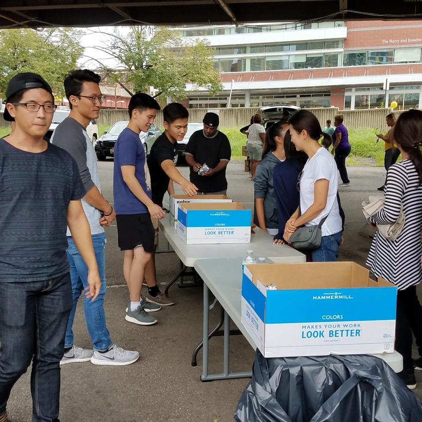 줄을 선 노숙자들에게 샌드위치와 물을 나눠주는 모습