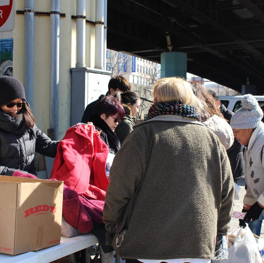 홈리스분들에게 겨울자켓 등 옷을 전달하는 모습