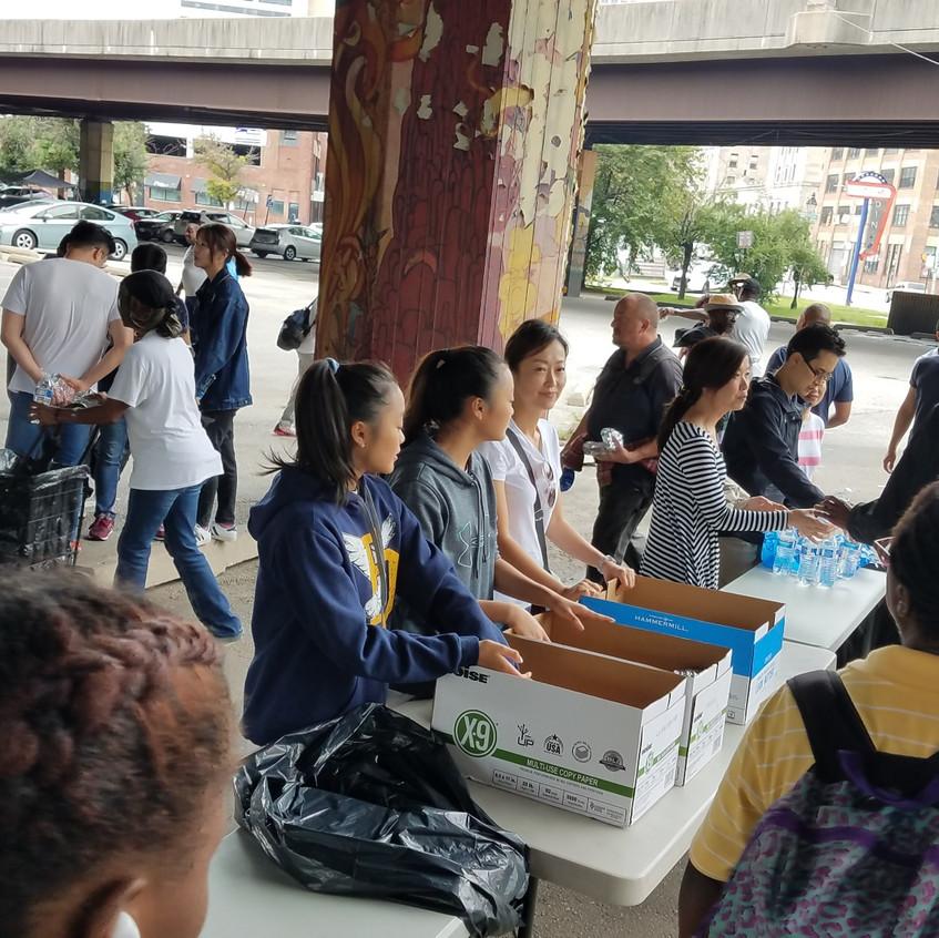 테이블 앞에 줄 서서 노숙자들에게 샌드위치와 생수를 나눠주는 모습