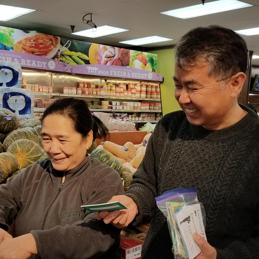 쇼핑 중인 고객에게 전도소책자를 전하고 있는 김학선 장로