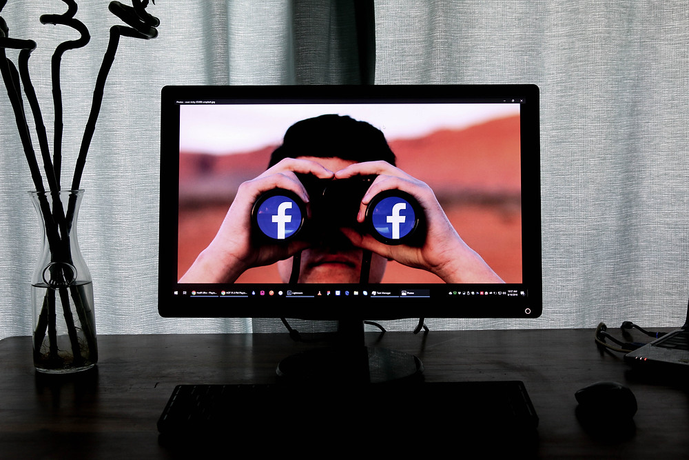 Laptop mit einem Facebook Hintergrund auf einem Tisch