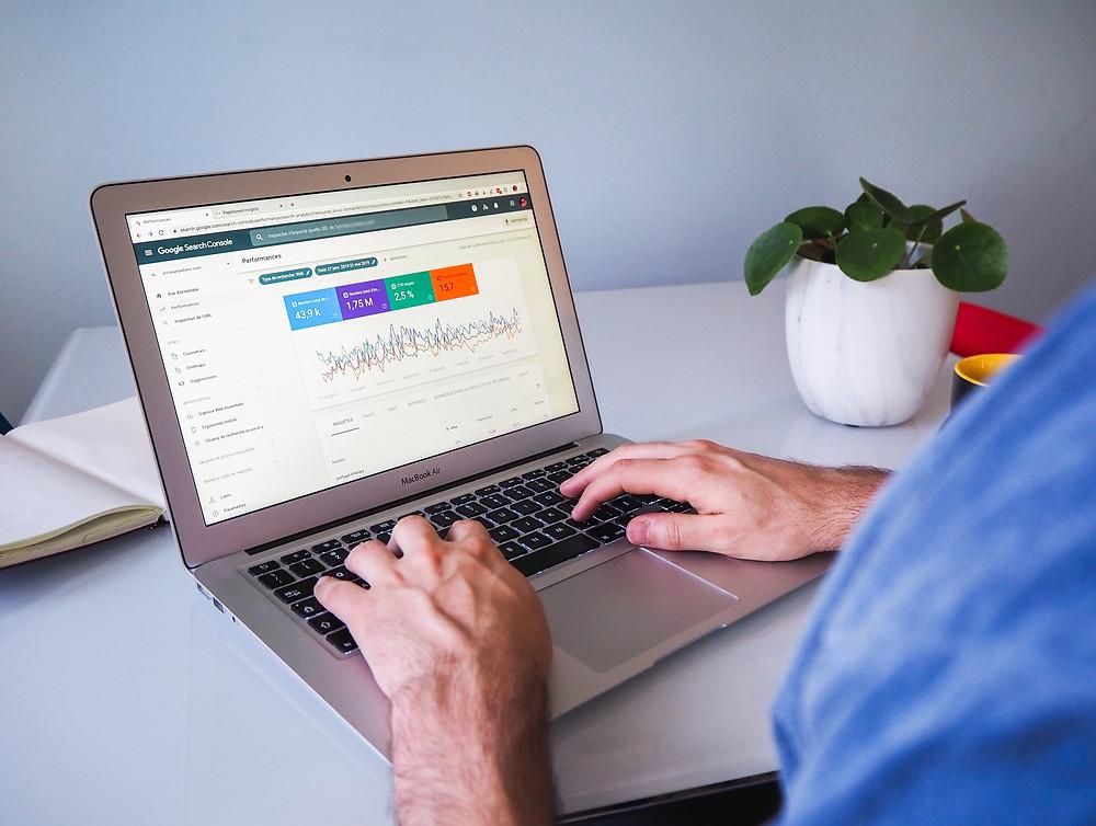 Mann am Laptop mit analytischer Grafik