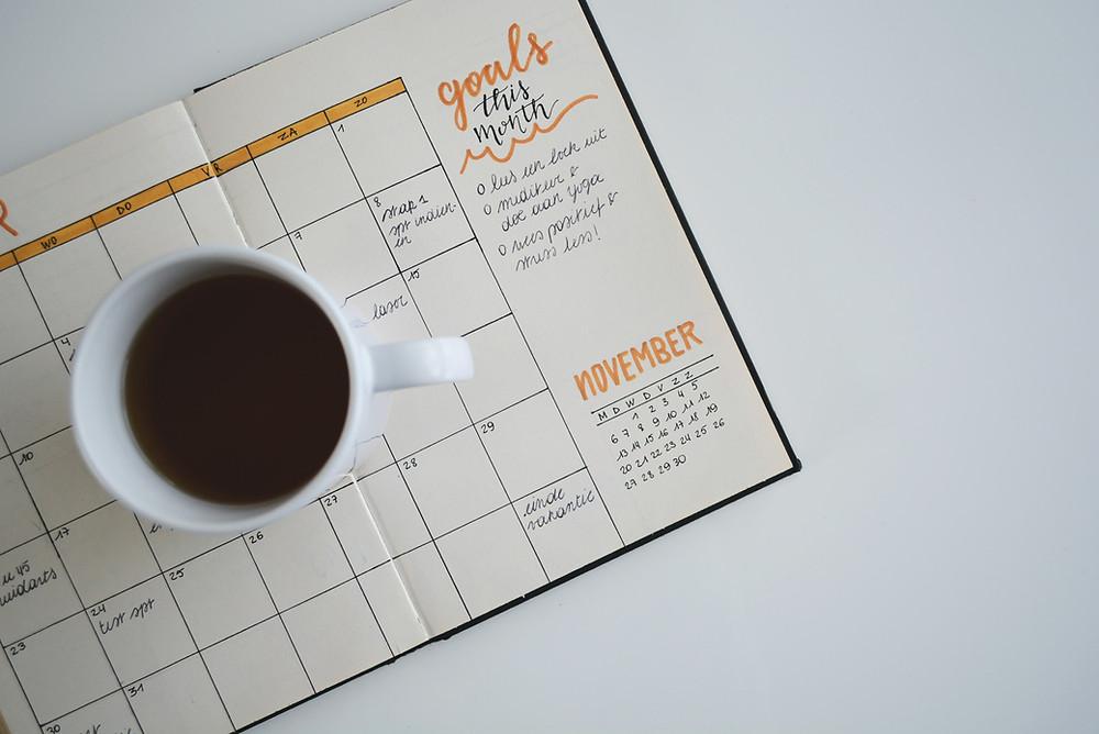 Tisch mit offenem Planer und Kaffetasse