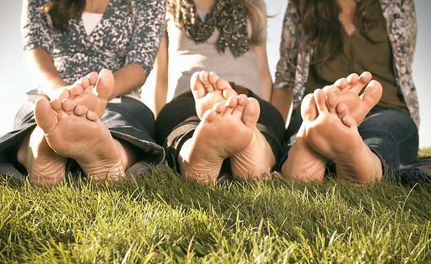 Picture of 3 pairs of different feet resting on the grass