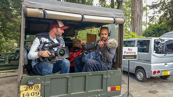 Location sound mixer and cameraman sitting in the back of a Toyota Land Cruiser