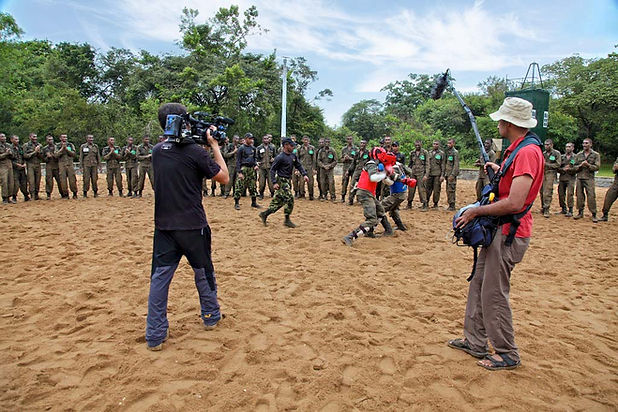 Cameraman and sound recordist filming military training camp in Sri Lanka.