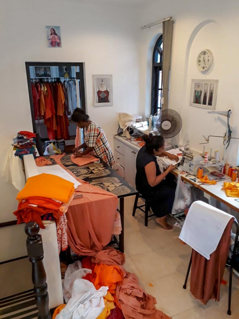 Two women making costumes. One woman on the right is sitting and working on a sewing machine. The woman on the left is standing and cutting patterns for sewing. There are costumes in the foreground.