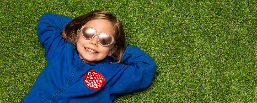 Cool child in sunglasses laying on grass