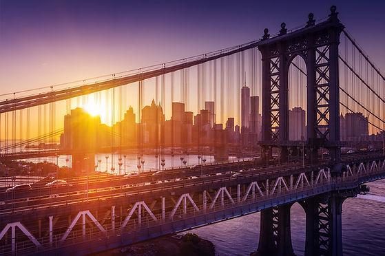 Brücke in Manhatten mit Autos, während die Sonne untergeht
