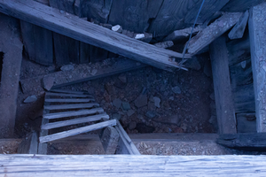 A view down into a dilapidated shed with broken wooden stairs and a collapsed wall.