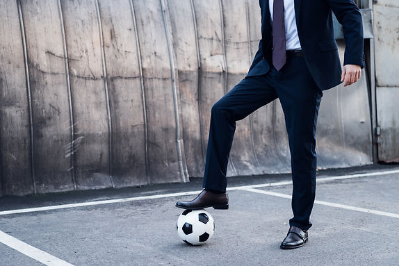 partial-view-of-businessman-in-suit-playing-soccer-H4EU7PH.jpg