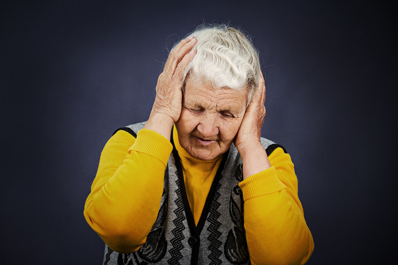 elderly lady holding her head