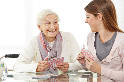 Caregiver playing cards with elderly lady