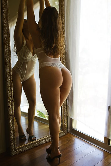 Woman posed by boudoir photographer in front of mirror