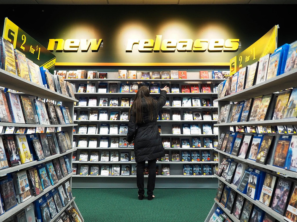 A woman selects a new release movie for viewing