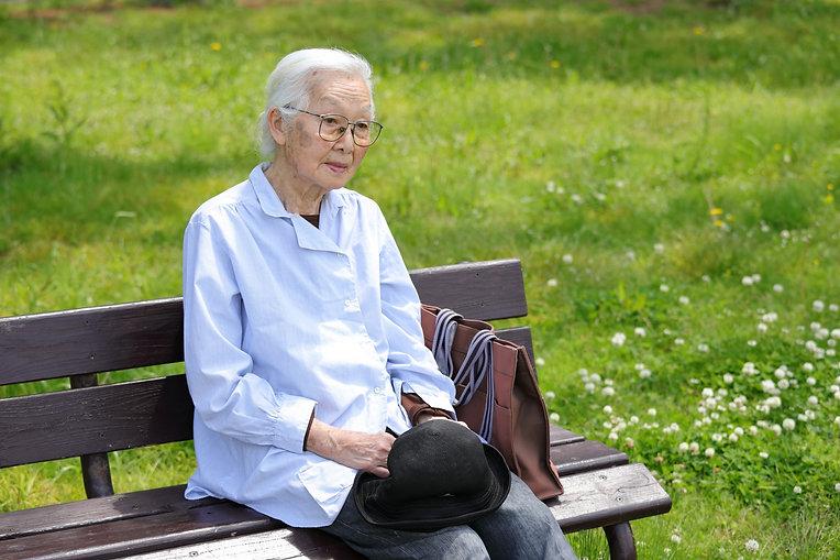 公園のベンチで休む高齢女性