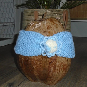 Bandeau tricoté bleu pastel avec une décoration crochetée et un pompon devant