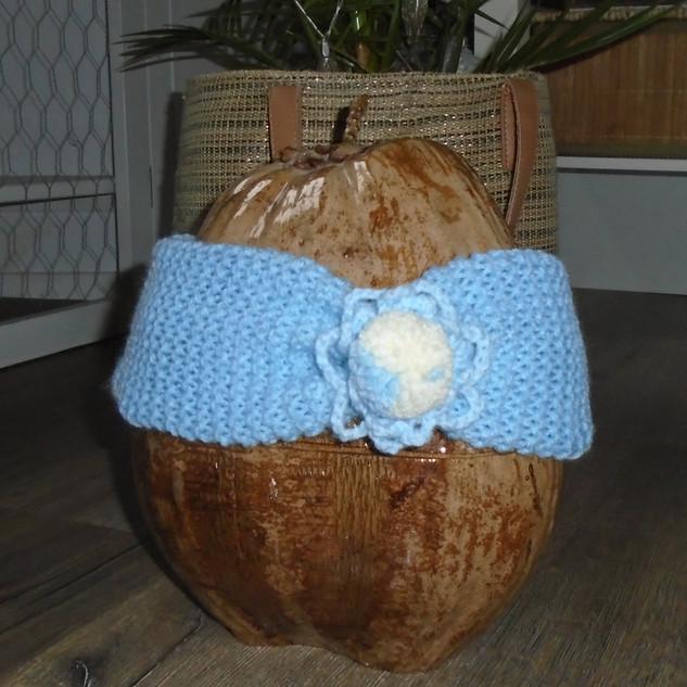 Pastelblauwe haarband met gehaakte versiering en een pompon aan de voorzijde