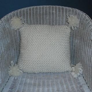 Coussin tricoté blanc aux pompons