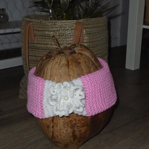 Bandeau tricoté rose/blanc avec une décoration crochetée et une perle devant