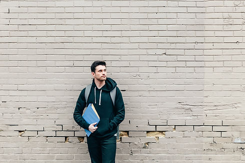 student-leaning-against-brick-wall.jpg
