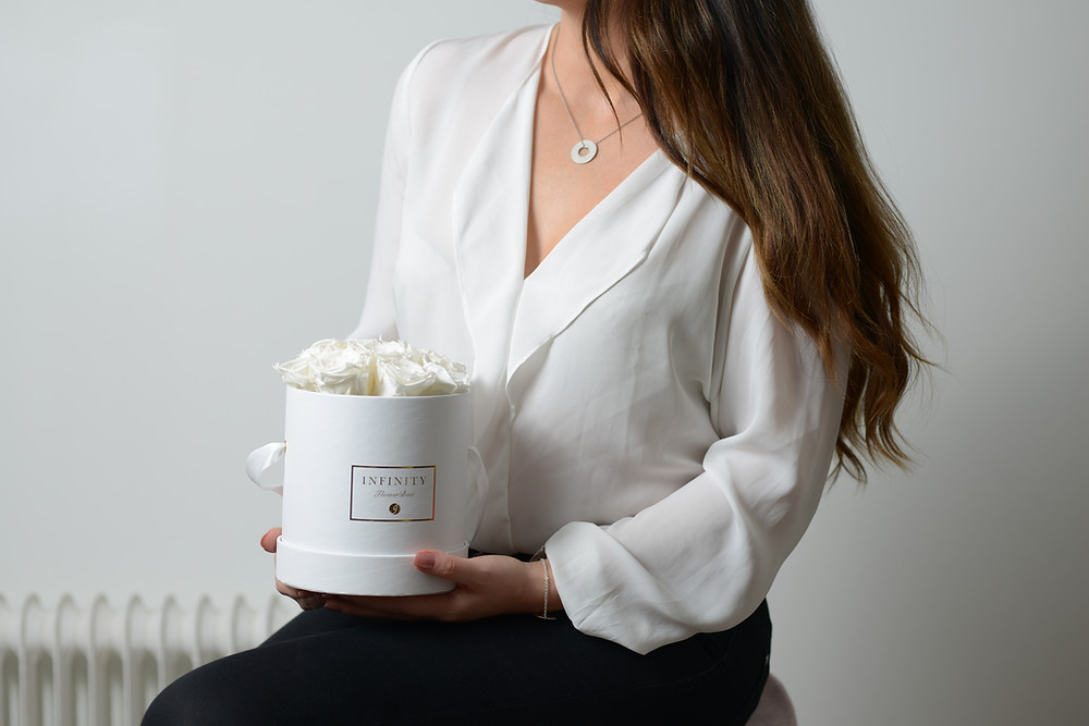 Pieni valkoinen laatikko valkoisilla ruusuilla