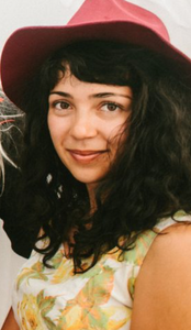 Profile photo of artist Joanna Keane Lopez wearing a red hat and yellow and white patterned blouse