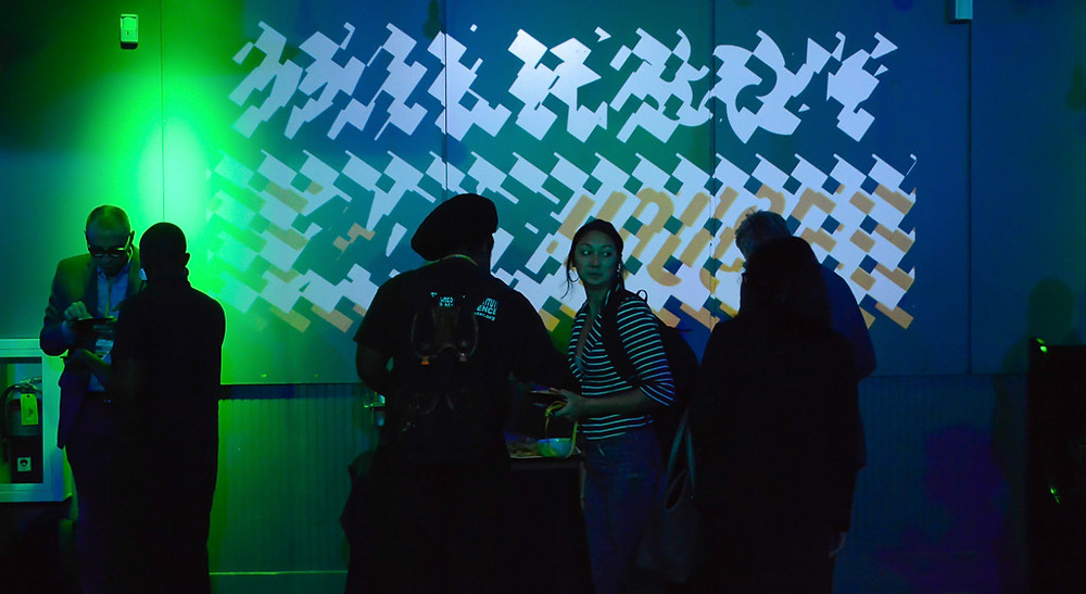 Five people socializing in dimly lit space in front of a graphic mural