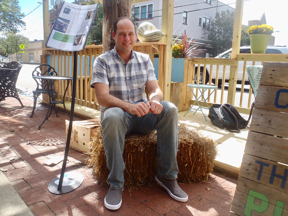 John Sullivan sits atop a block of hay in front of a wooden parklet structure on Walnut Street, Montclair.