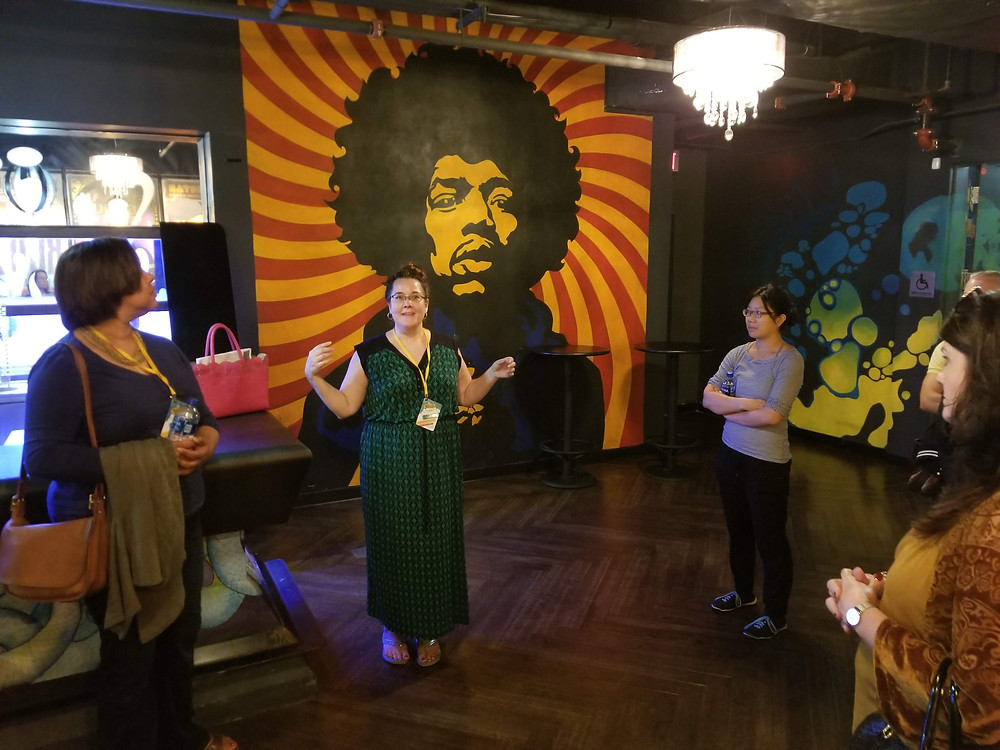Workshop leader in Silver Spring, Maryland standing in front of artwork that depicts Jimmy Hendrix.