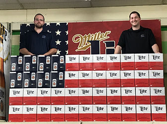 Employees posing with a beer display
